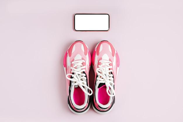 Nieuwe sneakers en smartphone mock-up op een roze achtergrond. app om binnen te trainen.