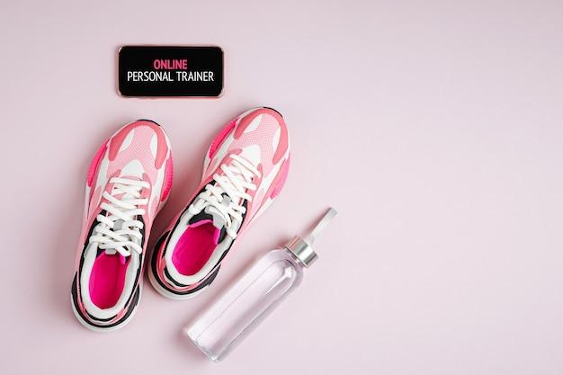 Nieuwe sneakers en smartphone op een roze achtergrond. app om binnen te trainen. online fitnessprogramma