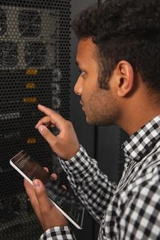 Nieuwe software. gerichte it-man die de serverkast onderzoekt en de tablet gebruikt