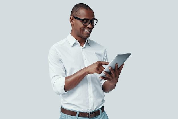 Nieuwe tablet onderzoeken. knappe jonge afrikaanse man die digitale tablet gebruikt en glimlacht terwijl hij tegen een grijze achtergrond staat