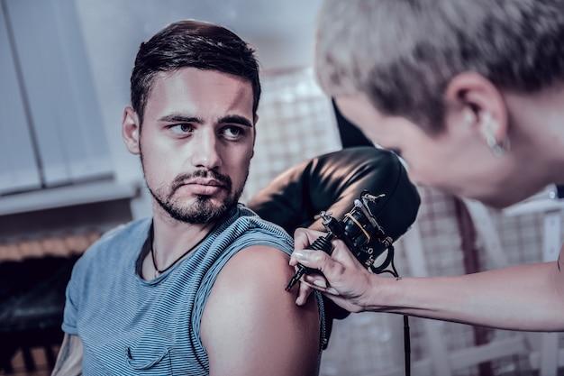 Nieuwe tatoeage beginnen. knappe bebaarde jongeman krijgt een nieuwe tatoeage van zijn bekende vrouwelijke artiest