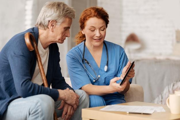 Nieuwe technologie. geweldige positieve medische werker die haar gadget gebruikt om haar toespraak te illustreren over de medicatie die meneer nodig heeft voor herstel