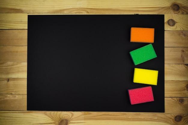 Nieuwe veelkleurige schuimsponzen op een zwarte achtergrond
