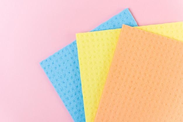 Nieuwe vodden voor natte reiniging. blauwe, gele en oranje vodden op roze.