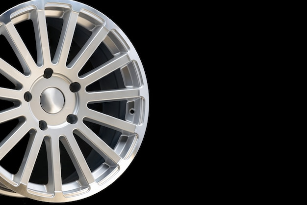 Nieuwe voertuigvelgen gemaakt van aluminiumlegering, multispaaks zilveren wiel, close-up op een zwarte achtergrond, kopie ruimte.