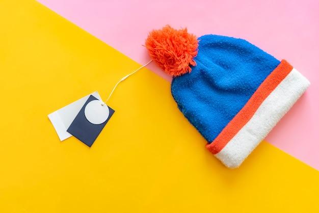 Nieuwe warme wol winter cap hoed met prijskaartje kopie ruimte creatief concept op roze en gele achtergrond f