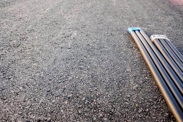 Nieuwe weg met rol van elektrische leidingen op zwart asfalt, kopie ruimte.