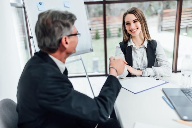 Nieuwe werknemer in kantoor. oudere baas biedt nieuwe manager vrouw.