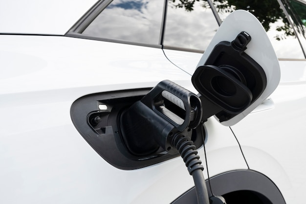 Nieuwe witte elektrische auto opladen bij een station