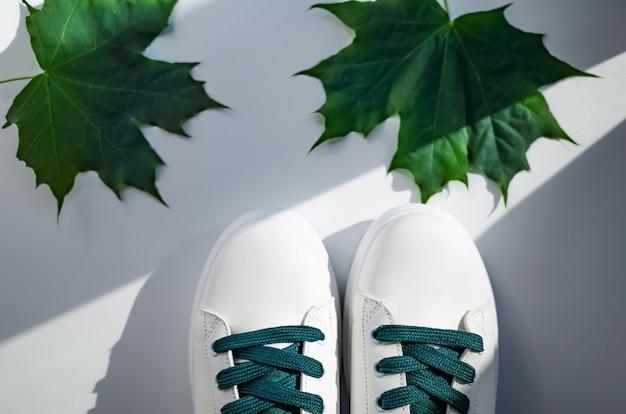 Nieuwe witte sneakers met groene veters met bladeren