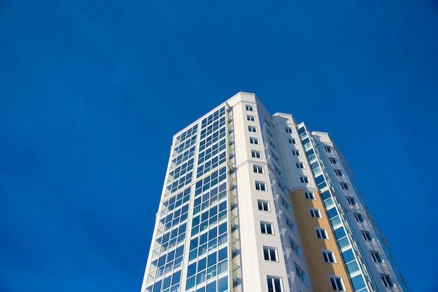 Nieuwe woningbouw met meerdere verdiepingen tegen de blauwe hemel