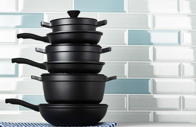 Nieuwe zwarte kookgerei tegen blauwe tegelmuur close-up