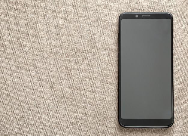 Nieuwe zwarte moderne cellphone die op de lichte ruimteachtergrond van het doekexemplaar wordt geïsoleerd. moderne technologie, communicatie en gadget