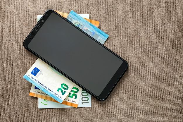 Nieuwe zwarte moderne digitale cellphone op geld euro bankbiljetten op achtergrond van de exemplaar de ruimtetextuur.