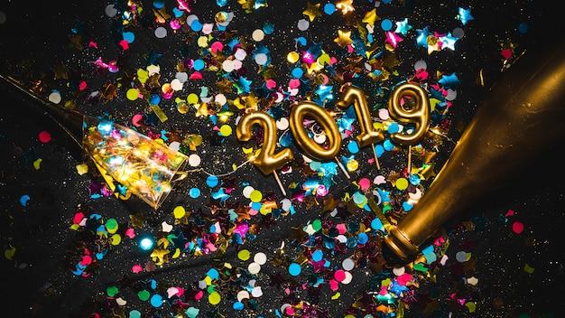 Nieuwjaar 2019 gevormde kaarsen op confettienstapel