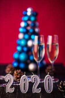 Nieuwjaar 2020-compositie met champagne en ruimte voor tekst tegen wazig kerstverlichting en boom. nieuwjaar en xmas concept