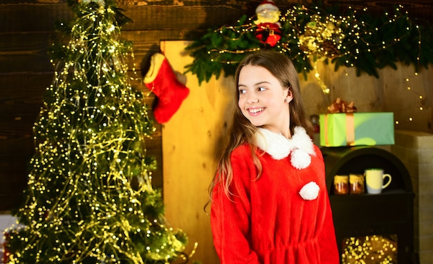 Nieuwjaar 2020 komt eraan. kerstboom met lampjes. mooie en gezellige kamer. klein meisje wacht nieuwjaar. kerstfeest zit erop. gelukkige jeugd. deze winternacht wees helder. santa helper elf bij kerstboom.