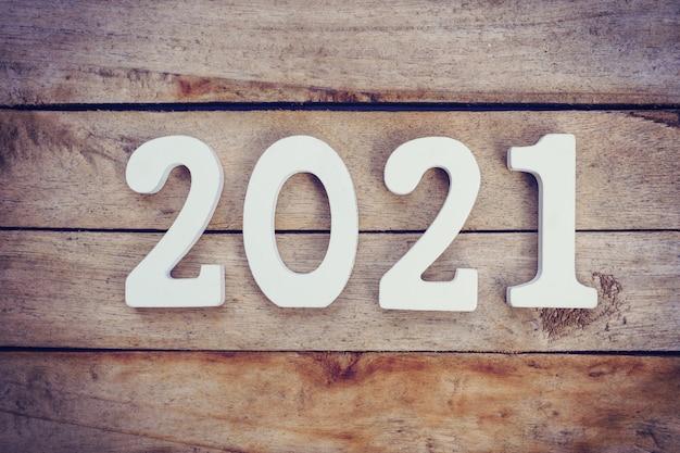 Nieuwjaar 2021 concept - houten nummer 2021 voor happy new year tekst op houten tafel.