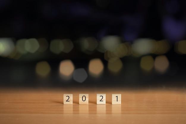 Nieuwjaar 2021 met houten kubus op tafel met bokeh achtergrond wazig.