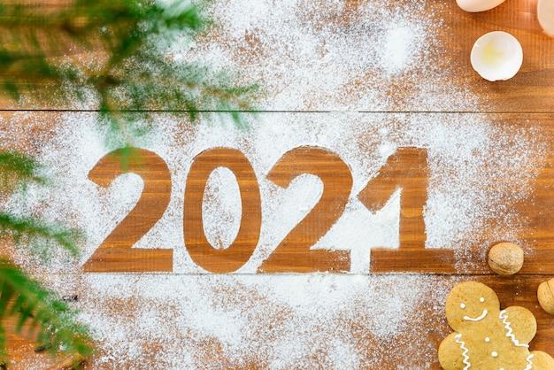 Nieuwjaar 2021. nummer op een bruine houten tafel rond kerstboomtakken en een peperkoekmannetje.