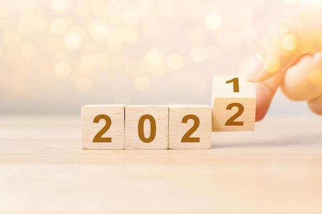 Nieuwjaar 2021 verandering naar 2022 concept hand flip-over houten kubusblok op houten tafel