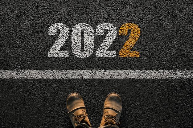 Nieuwjaar 2022, concept. de mens zet de eerste stap in het nieuwe jaar. herenschoenen op het asfalt in de buurt van de lijn met de nummers 2022, creatief idee.