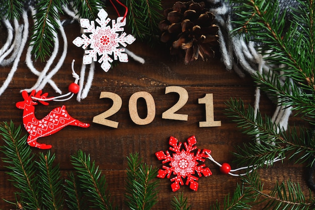 Nieuwjaar achtergrond met houten nummers, kerstmisspeelgoed, dennenappels en kerstboomtakken
