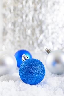 Nieuwjaar banner met blauwe, zilveren en witte kerstballen in sneeuw op abstracte winter achtergrond. xmas decoratie met kopie ruimte. vrolijk kerstfeest.