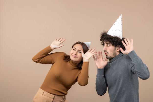 Nieuwjaar concept met bang jong koppel dragen nieuwjaar hoed meisje en jongen op grijs