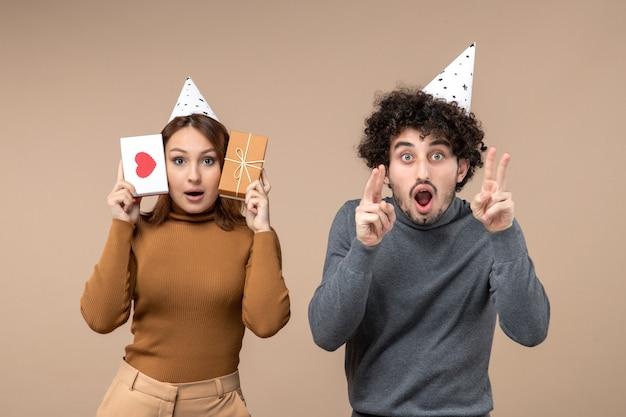 Nieuwjaar concept met jong koppel dragen nieuwjaar hoed meisje met hart en cadeau en kerel twee tonen op grijs