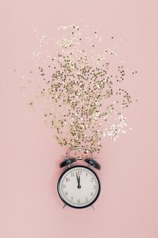 Nieuwjaar concept. wekker met gouden confetti