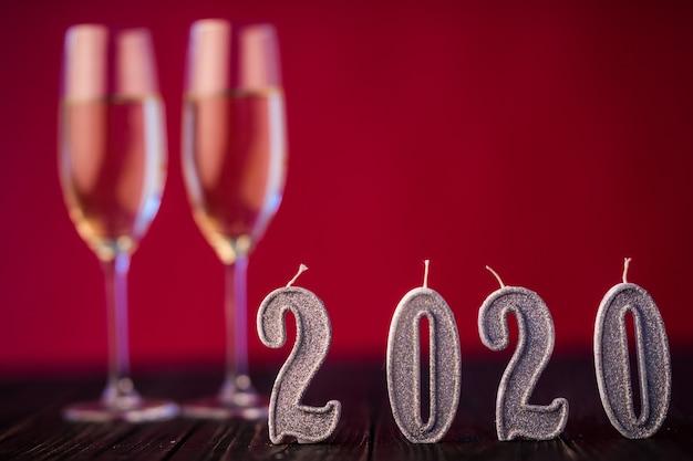 Nieuwjaar decoratie. twee gobelts met champagne met decoratie van kerstmis of nieuwjaar 2020 op rode lichte achtergrond