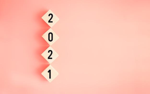 Nieuwjaar en doelen voor succesconcept, tekst 2021 op houten blokken op roze achtergrond.