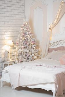 Nieuwjaar en kerst concept. kerstboom bij het bed in de slaapkamer..