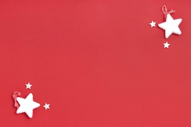 Nieuwjaar en kerst frame samenstelling. blanco vel papier met kerstversiering op rode ondergrond.