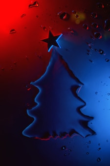 Nieuwjaar en kerstboom gemaakt van water met ster verlicht door neon, feestelijk concept. Premium Foto