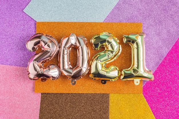 Nieuwjaar en kerstmis 2021 viering concept. folieballonnen in de vorm van cijfers 2021 en confetti. luchtballonnen. feestdecoratie vakantie.