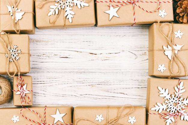 Nieuwjaar en kerstmis frame samenstelling. handgemaakte verpakt kerstcadeau dozen met decoratie op wit met lege copyspace voor uw tekst. bovenaanzicht, platliggend. afgezwakt