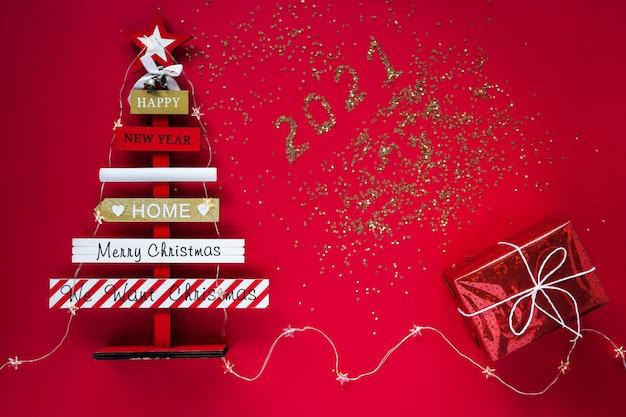 Nieuwjaar en kerstmis. houten abstracte kerstboom met wensen, verlichting en cadeau op een rode achtergrond.