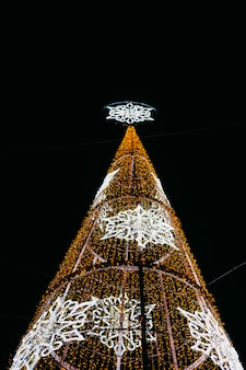 Nieuwjaar en kerstmis verlichtingsdecoratie van de stad. kerstboom met gele en witte leds 's nachts.