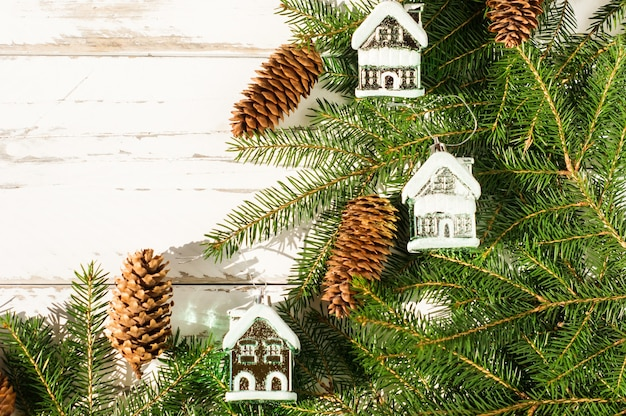 Nieuwjaar en kerstversiering op vuren takken. natuurlijke boskegels en speelgoed - besneeuwde huizen. witte houten achtergrond. bovenaanzicht.