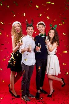 Nieuwjaar feest concept gelukkig plezier glimlachen vrienden bedrijf dragen sprookje carnaval kostuum kerstman herten kerstboom hoed bedrijf glas champagne vieren wintervakantie confetti