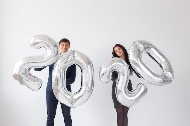 Nieuwjaar, feest en vakantie concept - liefdespaar met plezier met bord 2020 gemaakt van zilver