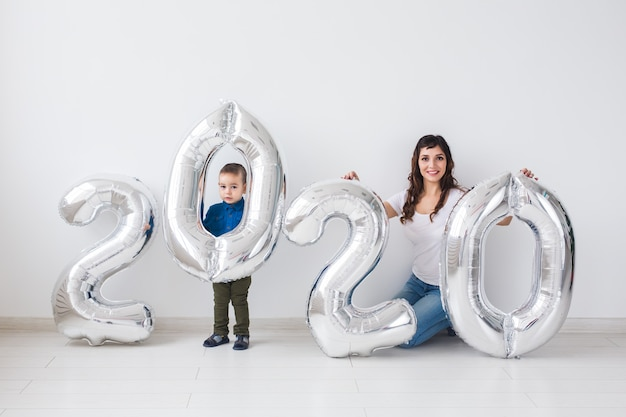 Nieuwjaar, feest en vakantie concept - moeder en zoon zitten in de buurt van teken 2020 gemaakt van zilveren ballonnen voor nieuwjaar in witte kamer