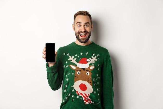 Nieuwjaar, feestdagen en viering. opgewonden bebaarde man in kersttrui, smartphonescherm tonend, staande op een witte achtergrond