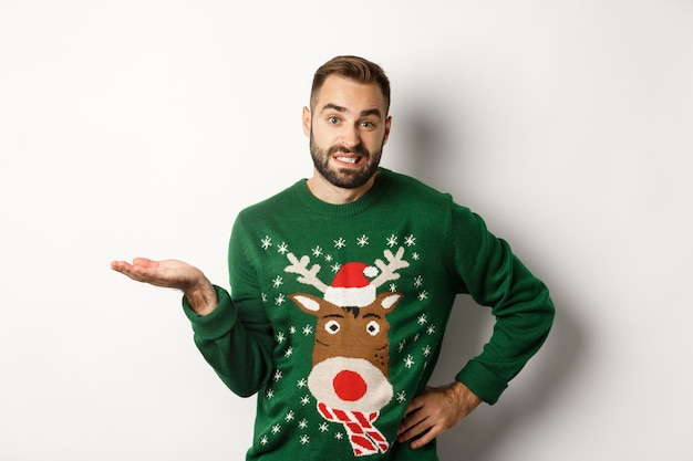 Nieuwjaar, feestdagen en viering. verwarde bebaarde man in grappige trui, schouderophalend en geen idee, weet het niet, ziet er ongemakkelijk uit, staat op een witte achtergrond