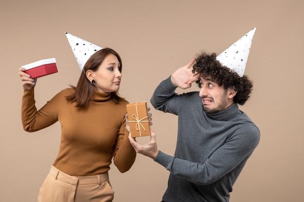 Nieuwjaar fotograferen met een gek jong koppel draagt een nieuwjaarshoed emotioneel meisje met hart en onzekere man met cadeau op grijs