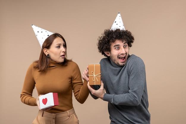 Nieuwjaar fotograferen met een jong koppel draagt een nieuwjaarshoed emotioneel meisje met hart en lachende man
