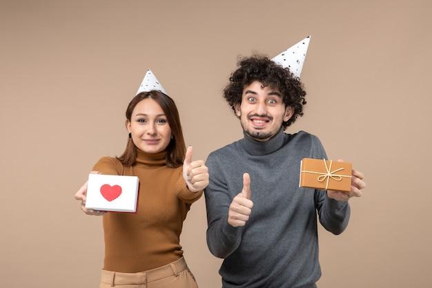 Nieuwjaar fotograferen met jong koppel dragen nieuwjaar hoed meisje met hart en man met cadeau en ok gebaar maken op grijs