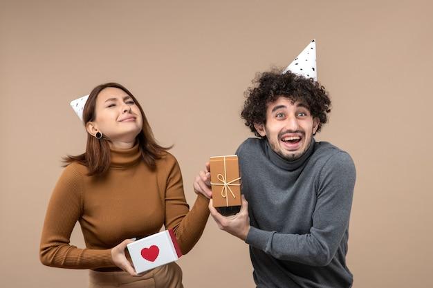Nieuwjaar fotograferen met jong koppel dragen nieuwjaarshoed boos meisje met hart en verwarde man met cadeau op grijs